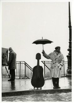A man on the side walk in rainy Paris. The man uses his umbrella to protect his cello case. This is the famous violoncellist Maurice Baquet. The image was taken by photographer Robert Doisneau in 1957.