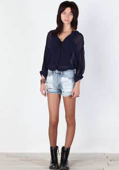 high-waisted slasher shorts, sheer button up, and combat boots.