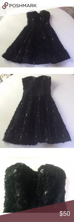 """Bebe floral dress rosette black mini full s m This is a dress by Bebe. It has rosettes w sequin centers. size and main brand label are missing, there is interior brand label. I am guessing based on how it fits me, it is a S or M. Please use measurements. boned bust w zip back, full skirt. It is lined, cups have structure, tacky strip along top to keep up. does not come w straps, has ribbons sewn in to hook them to. Dry clean.  Arm pit to arm pit: 14""""-17"""" I am a 34 C it is a bit snug on me…"""