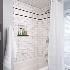 Smoke-colored grout and a row of subways turned on end and bordered with black trim add character to this tub alcove. | Photo: Ryan Kurtz | thisoldhouse.com