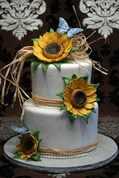 "- 8"" and 6"" rounds covered in fondant. Gumpaste sunflowers and leaves. Non-edible butterflies and raffia. :-)"