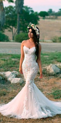 a strapless blush mermaid wedding gown in blush with white lace appliques and a train