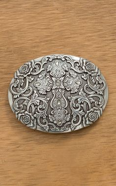 "- Antiqued Silver Oval Buckle - Cross Center Design with Rhinestone Accents - Rose Filigree Detail - Buckle Measures: 4"" x 3.25"" - 1.5"" Swivel This beautiful antiqued silver oval buckle from Nocona fe"