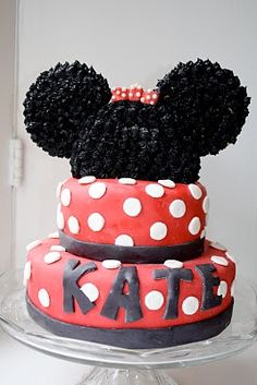 Minnie Mouse Birthday cake & decorations - this cake topper is made from a half round + two big sugar cookies attached with skewers, & black frosting stars piped on.
