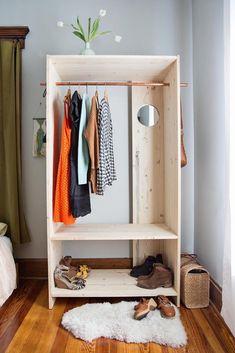 Armário aberto de madeira simples! Invista em móveis simples. Um colchão confortável, uma arara de roupas ou cabideiro, um criado-mudo, e se houver espaço, uma pequena bancada, já tornam o ambiente suficientemente prático.