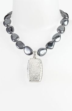 Mirror-shine nuggets connect a handcrafted collar necklace centered with a hammered silver tile. By Simon Sebbag; made in Israel.