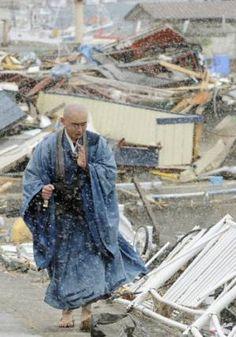 震災、雪降る中祈る僧侶