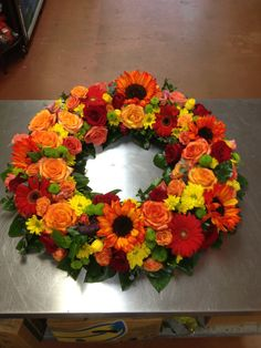 Fall colored fresh flower wreath. Orange Sunflowers, Roses, Red Gerbera Daisies, Yellow Daisies, Green Button Poms. www.darlingflowers.net  Darling Flowers