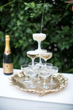 little coupe towers on silver platters, on a black tablecloth, with bowls of berries, mint leaves, pomegranate seeds and peach slices for guests to add into their champagne.