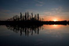 Dark island near bright setting sun by Horia Varlan, via Flickr