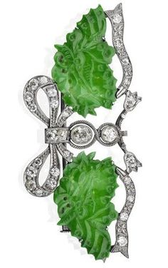 An early 20th century jadeite and diamond brooch. Formed as a pair of carved jadeite leaves with a diamond-set bow motif between, width 62mm, the jadeites measuring approximately 25 x 16 x 1mm, mount bearing Chinese marks.