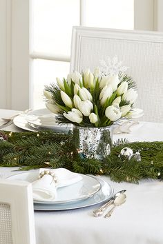"""Bring elegant winter whites to your Christmas dinner table! Fresh garland and a simple bouquet make a unique holiday """"table runner""""."""