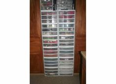 12 by 12 clear drawers stacked.  Solid color paper on bottom half of one side and patterned paper on bottom half of other side.  Ribbon and fibers are in upper drawers.