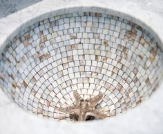 Bathroom Tile Sink with Decorative Drain Cover. Shop the Look: http://www.completely-coastal.com/2017/01/coastal-powder-room-with-decorative-starfish-sink-drain.html