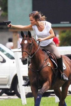 Two things are very apparent in this photo, she knows how to ride a horse, and she knows how to shoot a pistol.