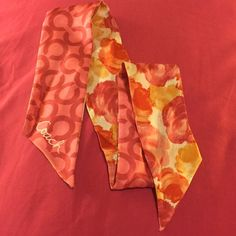 Coach floral scarf Authentic coach silk ponytail scarf. So cute tied to handbags! Floral pattern in warm colors on one side; pink signature c print on other side. matching coach umbrella in pic has been sold! Coach Accessories Scarves & Wraps