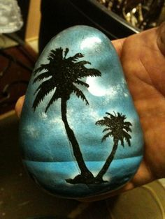 Cool blue sunset with palms painted on a rock.
