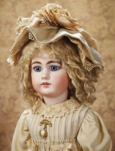 "Closed Mouth Child,939,by Simon and Halbig 25"" (64 cm.) Bisque socket head with flattened solid dome,long- faced modeling with full cheeks,large blue glass paperweight inset eyes with spiral threading,dark eyeliner,dark painted lashes,thick brush-stroked brows,accented nostrils and eye corners,closed mouth with defined space between the outlined lips,pierced ears,Sonneberg composition and wooden fully-jointed body with straight wristsMarks: S 15 H 939. Comments: Simon and Halbig,circa 1890."