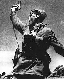 A Soviet junior political officer armed with a Tokarev TT-33 Service Pistol urges Soviet troops forward against German positions during World War II.