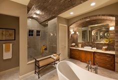 bathroom with brick arched ceiling, large shower with glass front