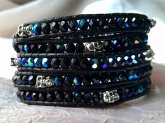Jet black beads with a brilliant blue iris finish, and silver skull beads interspersed randomly. This leather wrap bracelet is a great gothic