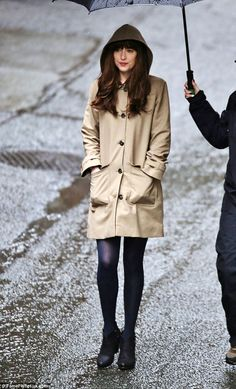 Pretty: She wore natural make-up and a pink lip gloss as she tried to stay sheltered in the rain
