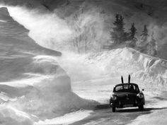 A Porsche drives up the road to Zürs in 1953, photo by Hans Truöl. Zürs is in the Arlberg region of Austria.
