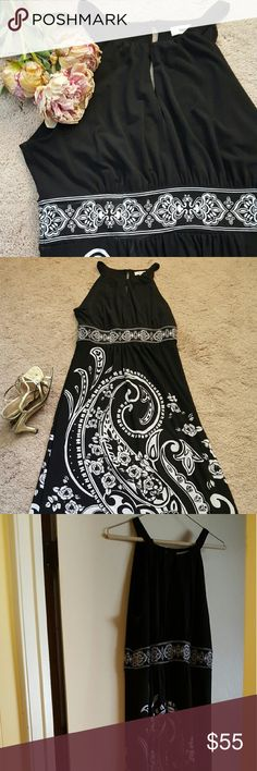 "WHBM keyhole maxi dress Long black halter-style maxi dress with keyholes in front and back. Scrolled white rose pattern climbs up the bottom of the skirt. Dress is in excellent condition. Size says small but dress is extremely stretchy. Easily would fit medium as well. Bust 17"" Length 59"" White House Black Market Dresses Maxi"