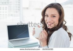 Portrait of a smiling businesswoman with coffee cup in front of laptop in a bright office - stock photo