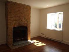 Exposed brick chimney breast and wood burning stove. Flag bricks.