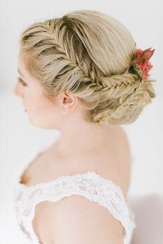 Seitlich geflochtene Brautfrisur mit Dutt am Hinterkopf und frischen Blumen
