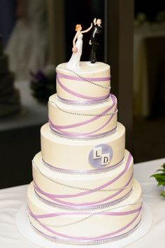 """The couple's Words With Friends theme also popped up in their wedding cake. Ciao Bella Cakes baked a five-tier ivory confection wrapped in whimsical purple ribbon and silver beading as two """"L"""" and """"D"""" Words with Friends inspired tiles accented the center tier. For a fun touch, their cake topper also included Leah and Dave giving each other a high-five using our figurines. Photo credit: George Street Photo & Video Bakery: Ciao Bella Cakes. https://www.theknot.com/real-weddings/"""