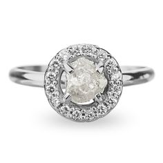 Halo rough diamond engagement ringThis ring features a uncut, raw conflict free diamond set in a beautiful halo of faceted white diamonds. The rough diamond used for this ring has wonderful little crystals all over the surface which pic...