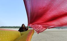 An Indian Hindu pilgrim holds up saris to dry in the wind after taking a holy dip in Gangasagar, some 155 kms south of Kolkata. Photography by Dibyangshu Sarkar.