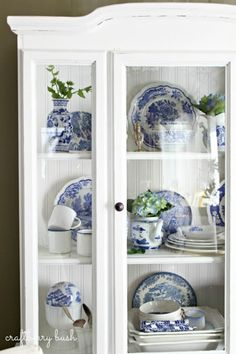 blue and white transferware china dishes in white hutch cabinet