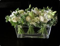 Beautiful green and white bouquets comprise a chic floral arrangement when placed in a sleek glass vase of water.-  polux fleuriste