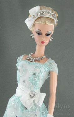 Elegant embroidered lace retro sheath and hat for Victoire and Silkstone dolls.  White satin sweetheart sheath with a soft blue and silver lace overlay and gathered capped sleeves. Waist is embellished with an attached gathered white satin sash with bow and faux diamond jewel. Coordinating white hat with faux diamonds and bow adn white gloves complete the ensemble. Snap back closure.  Doll, shoes and jewelry are not included.