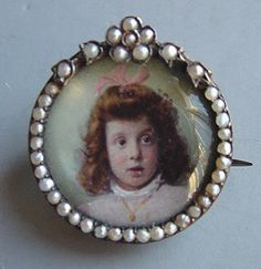 antique portrait on celluloid surrounded by seed pearls ... could be a 'momento mori' or mourning remembrance pin.