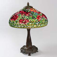"This is not contemporary - image from a gallery of vintage and/or antique objects. ""Peony"" Tiffany Lamp  A Tiffany Studios New York mottled glass and patinated bronze ""Peony"" table lamp. The shade features a bouquet of crimson peony blossoms with green leaves against a light blue ground accented with mauve, golden, and blue highlights and sits atop a decorated ""Library"" base with reticulated bronze work."