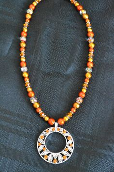 Fun and bright orange and silver necklace with larger silver leaf pendant. Both necklace and pendant include orange Swarovski crystals. $22