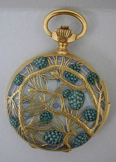 This charming pine tree-themed 1900 Lalique watch case if made of gold and teal-colored enamel.  (Les Arts Décoratifs)