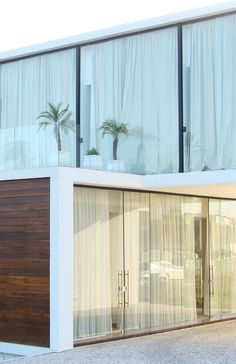 residential architecture: white modern home house with glass balcony balustrade, wooden timber garage door, floor to ceiling full length window and doors, white sheer drape curtains
