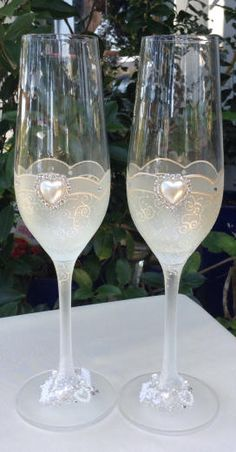 Champagne Toasting glasses for weddings and special occasions. Perfect for any occasion, this set of toasting glasses consists of a pair of hand-painted crystal champagne flutes painted a sheer shimmering cream colour with a delicate scrolling design. The centre of the glass features a