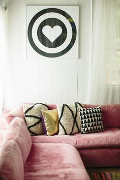 Style At Home: Jen Coleman Of Ascot + Hart on The Glitter Guide -- Love this comfy and pretty L-shaped pink velvet sofa topped with graphic black and white patterned Moroccan pillows, white paneled walls and a bold heart bullseye poster.