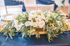 Jof Panlaqui Photography of a White Button Events wedding,  white wedding flowers of white lisianthus, white spray roses, white wax flowers, white roses, white freesia, and seeded eucalyptus in a hand painted golden container.  It is the perfect elegant companion to the navy and soft champagne gold colors of the wedding.