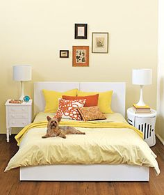 Decorating Tricks for Your Bedroom:   Don't be afraid to pair up unlike pieces, as with these bed tables. A short stack of books serves to even up the lamps.