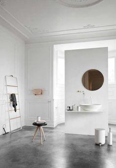 joli salon blanc avec sol en beton ciré gris et moulures decoratives et corniche…