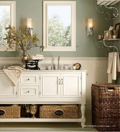 Gratifying Green by Sherwin Williams | Light sage green bathroom color with white and wicker accents