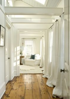 love the antiqued wooden floors and the white drapes and beams!