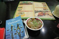 Dani feuillette son guide pendant un déjeuner vietnamien...